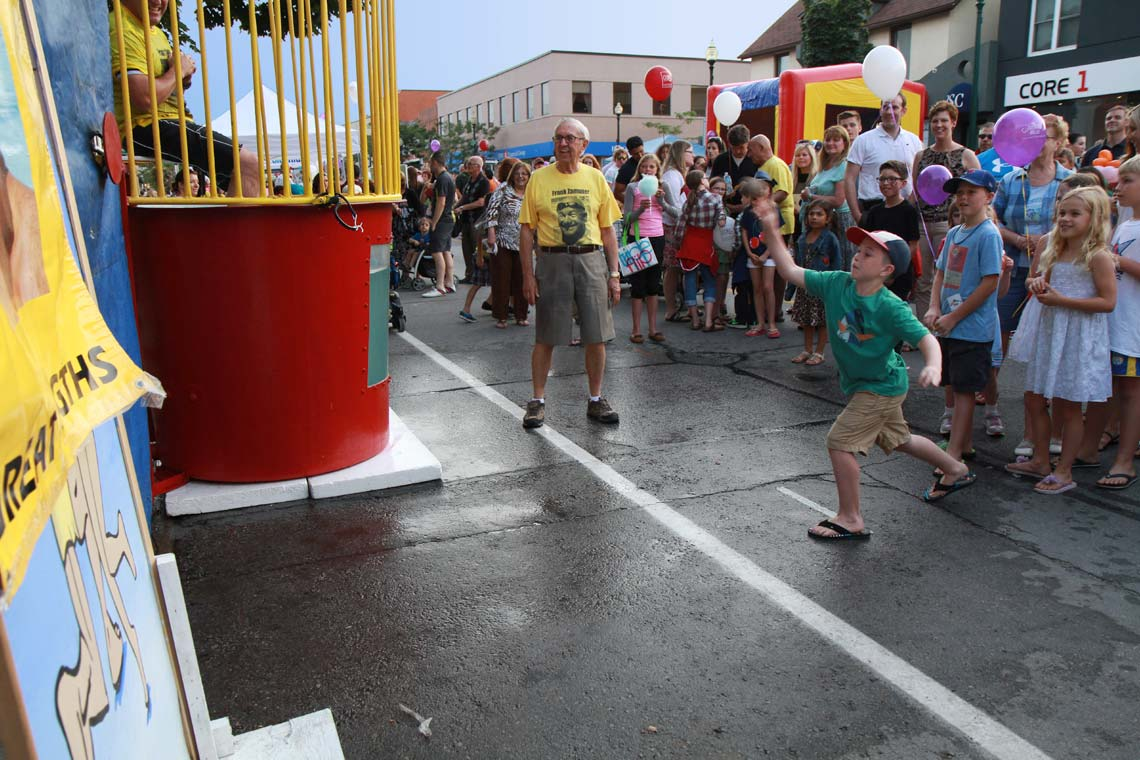 Child throwing baseball at a dunk tank
