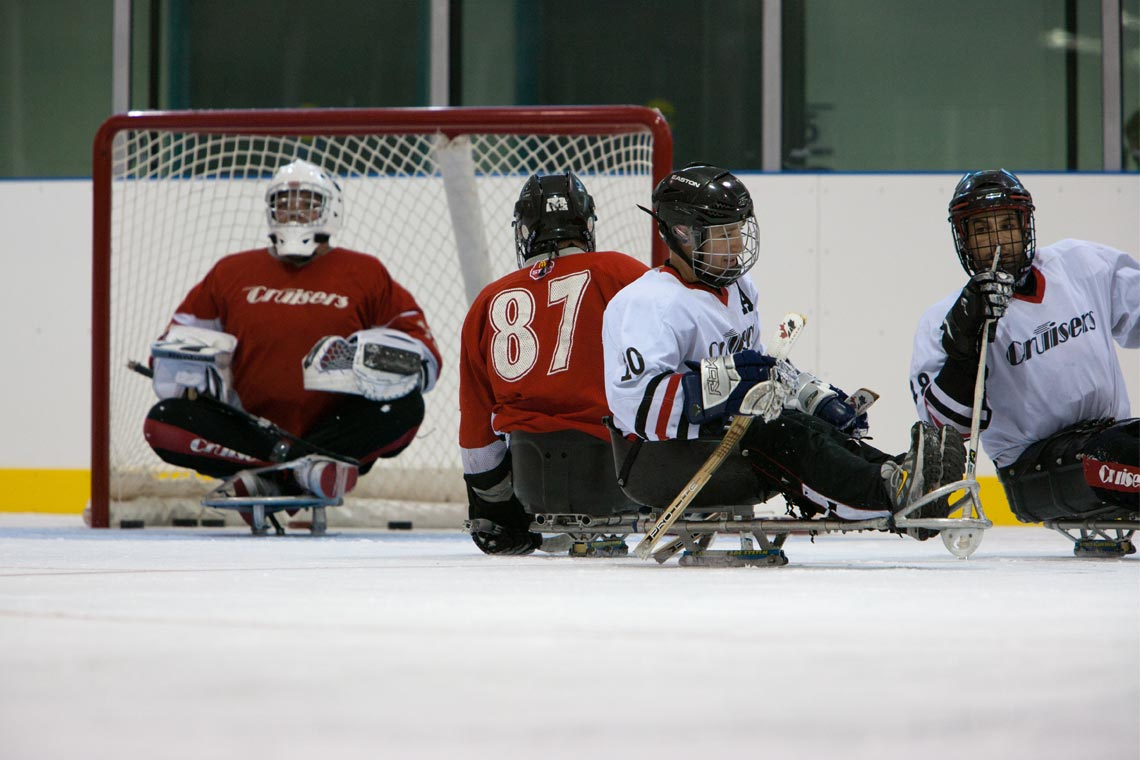 People playing sledge hockey