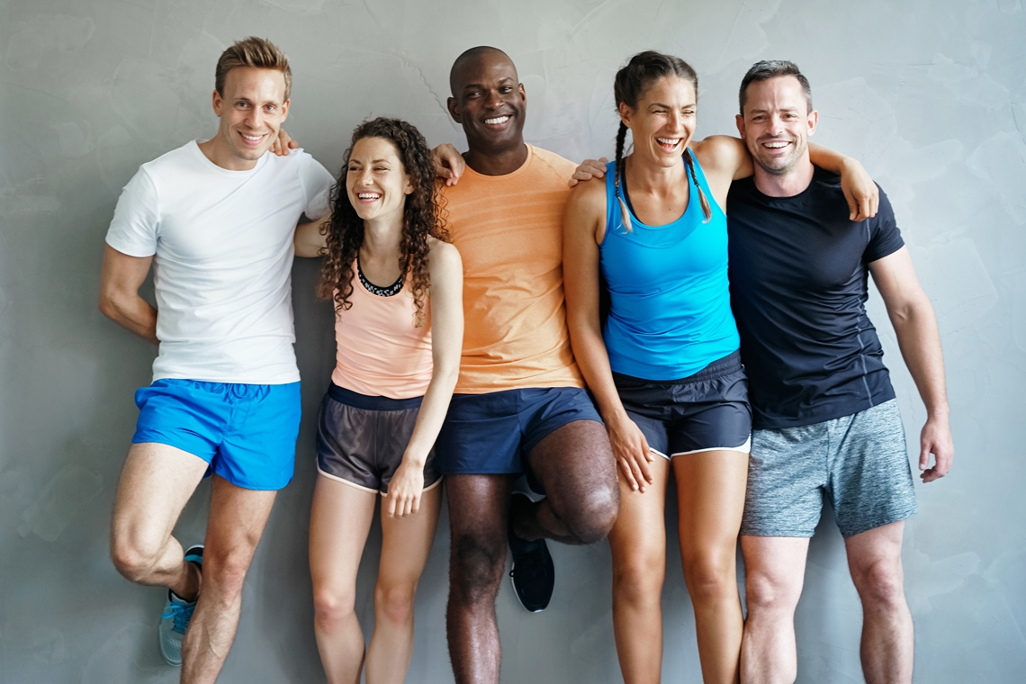 Smiling adults dressed to exercise/play a sport together.