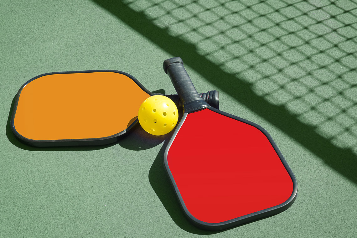 Image of pickleball paddles and ball on the ground.