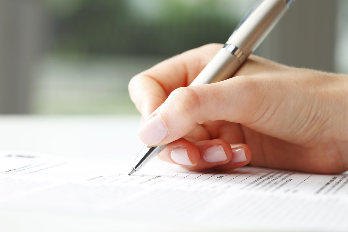 Image of person signing a document.