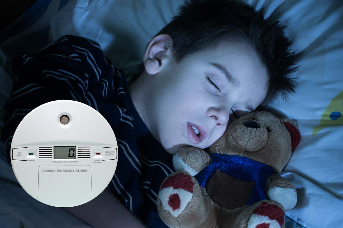 Boy sleeping in room with carbon monoxide alarm